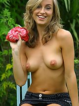 Melanie in the garden wearing a red tie-die top with a pinstripe skirt with white cotton panties.
